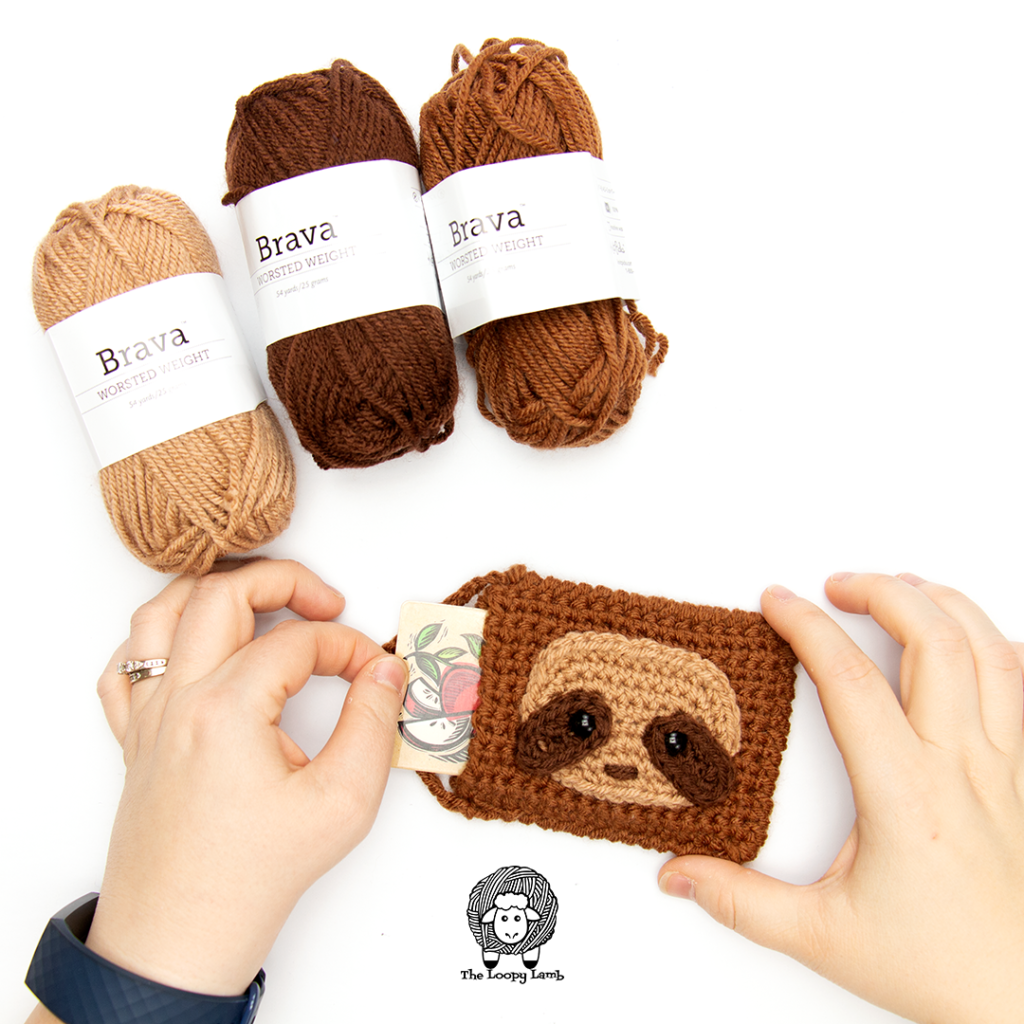 hands taking a gift card out of the diy gift card holder made with this free crochet pattern