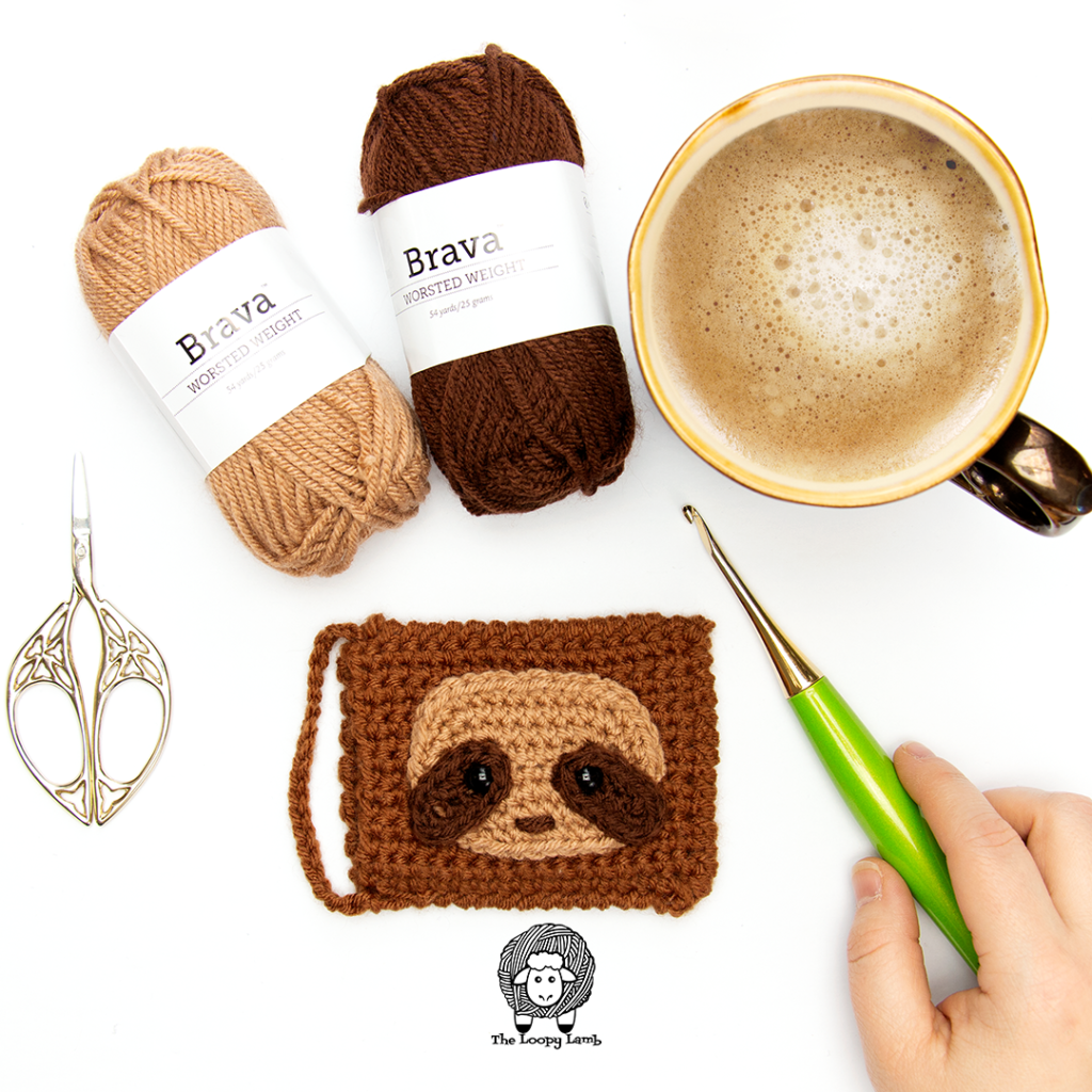 Sloth Crochet Gift Card Holder in a flay lay with Brava Worsted Weight Yarn and a crochet hook