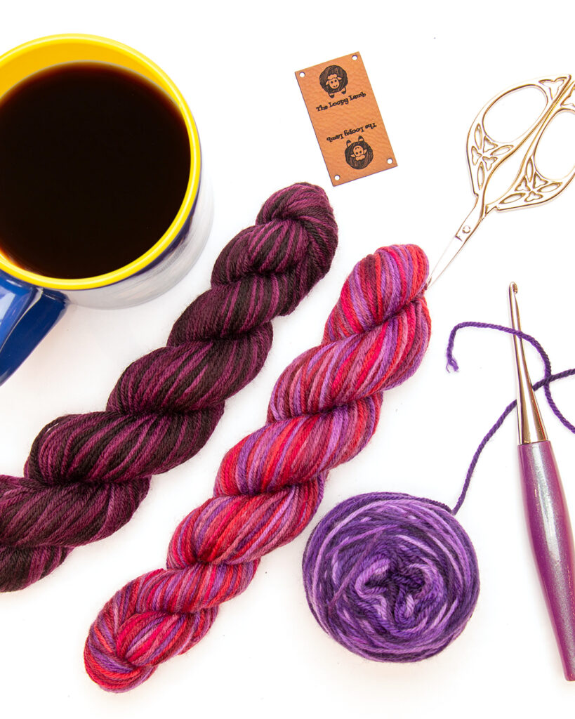 Two mini hanks of yarn in a flat lay with a furls odyssey crochet hook, scissors and a coffee.