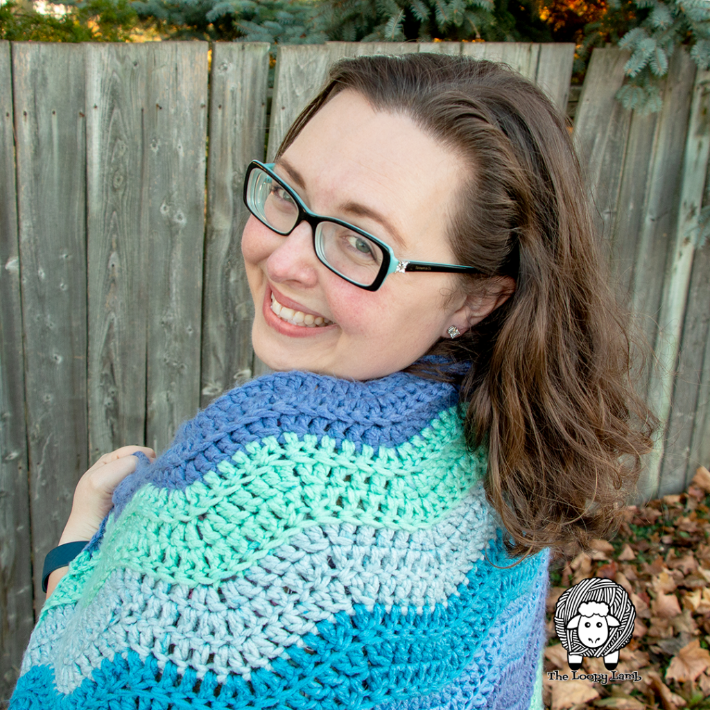 Woman smiling, looking over her shoulder with a crochet blanket made with this free crochet pattern on her shoulders.