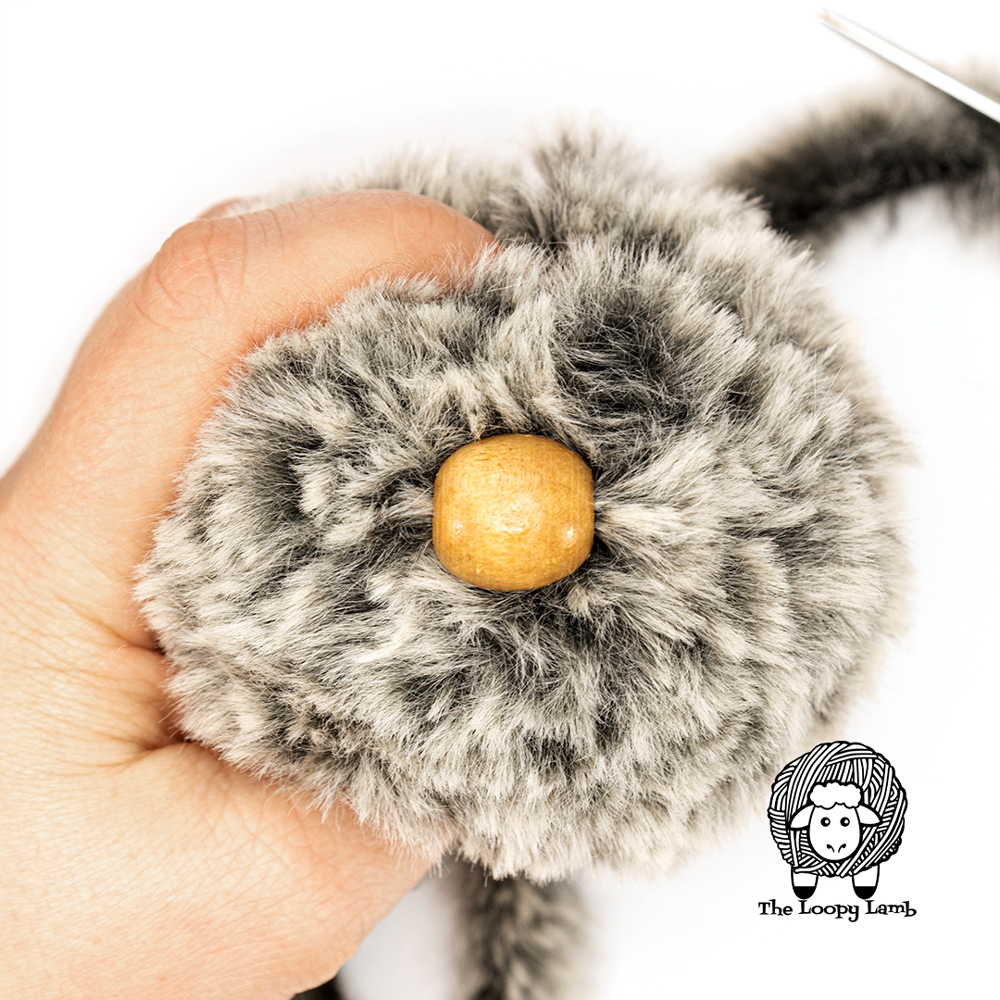 bead sewn onto side of faux fur yarn pompom