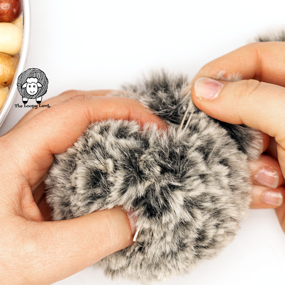 needle coming out the side of a faux fur yarn pompom