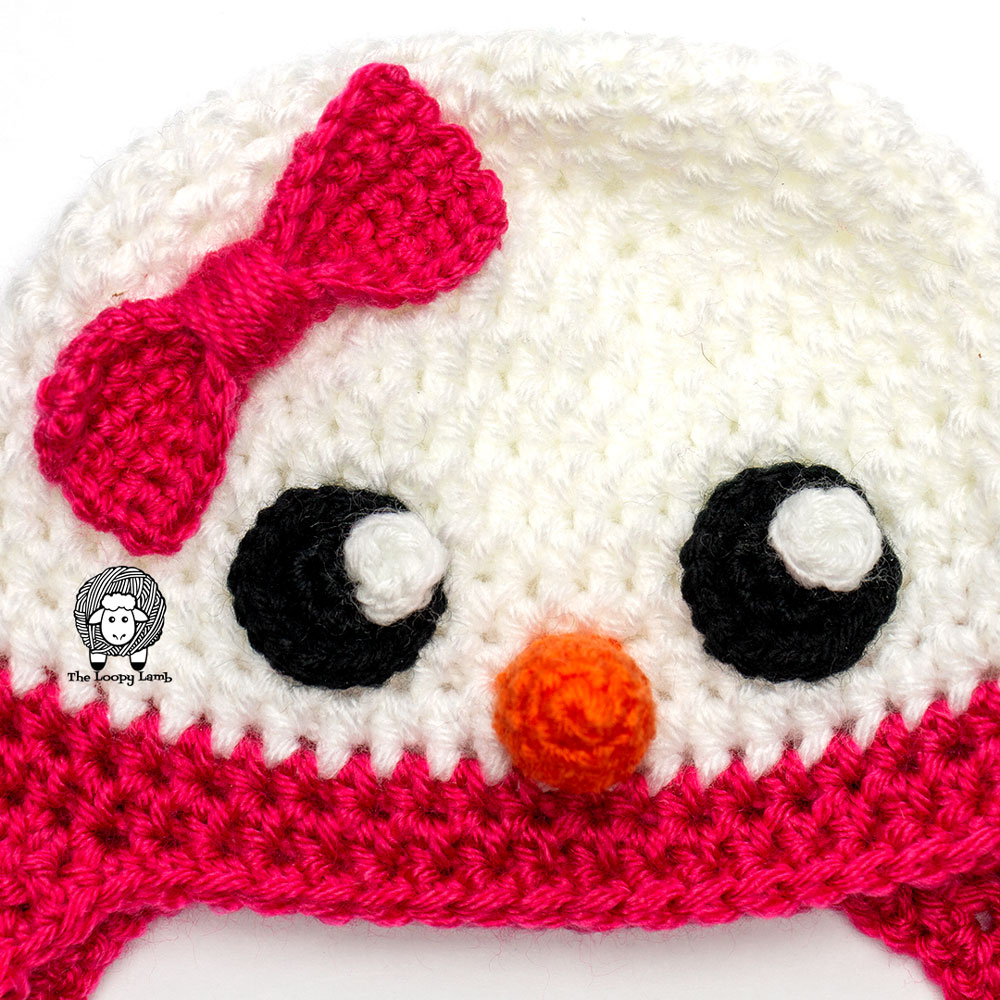 Close up of eyes, nose and bow on this crochet snowman hat pattern