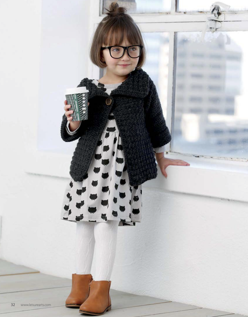 Child wearing a black crochet sweater, holding a coffee