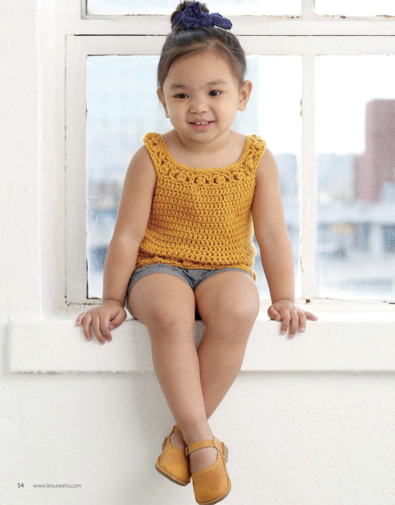 Toddler wearing a yellow top made using the crochet patterns for toddlers in Lil' Hipsters