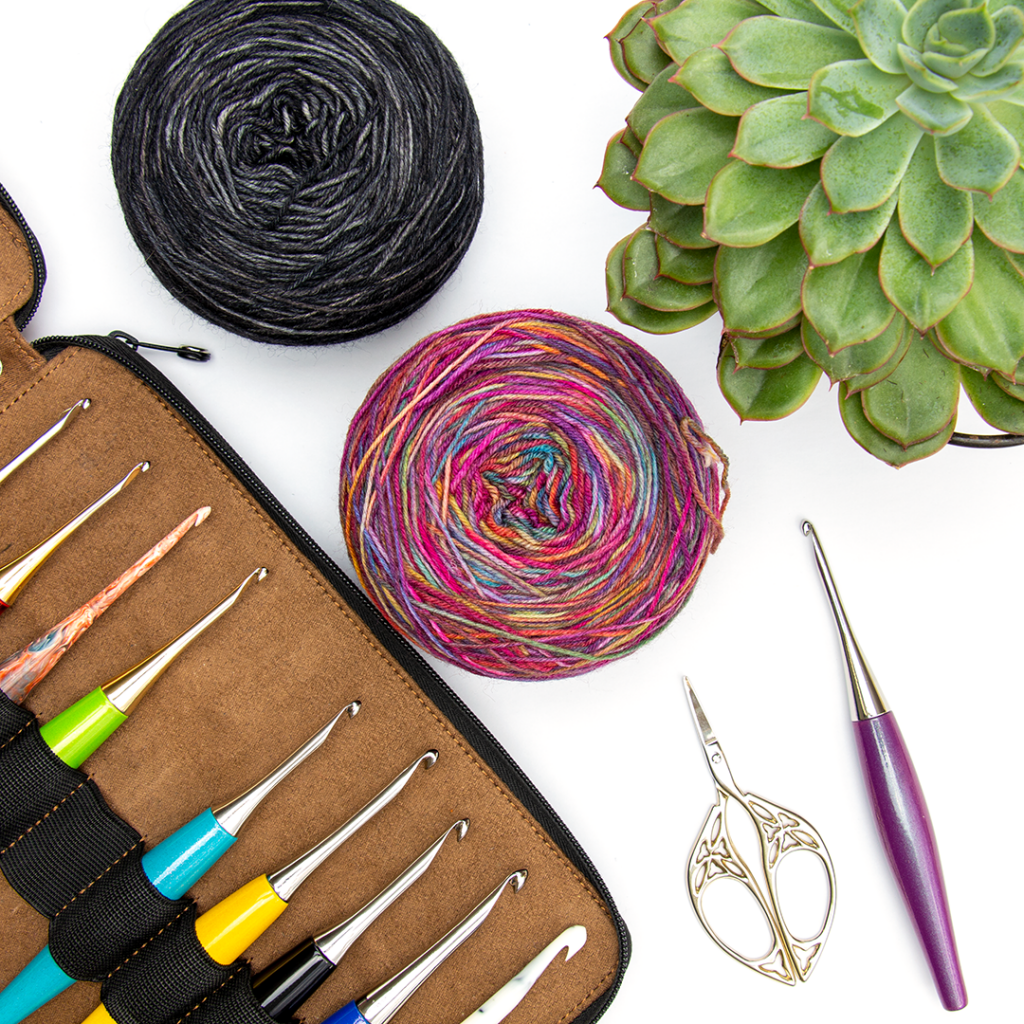 Muse Hand Painted Fingering yarn cakes in a flat lay with crochet hooks