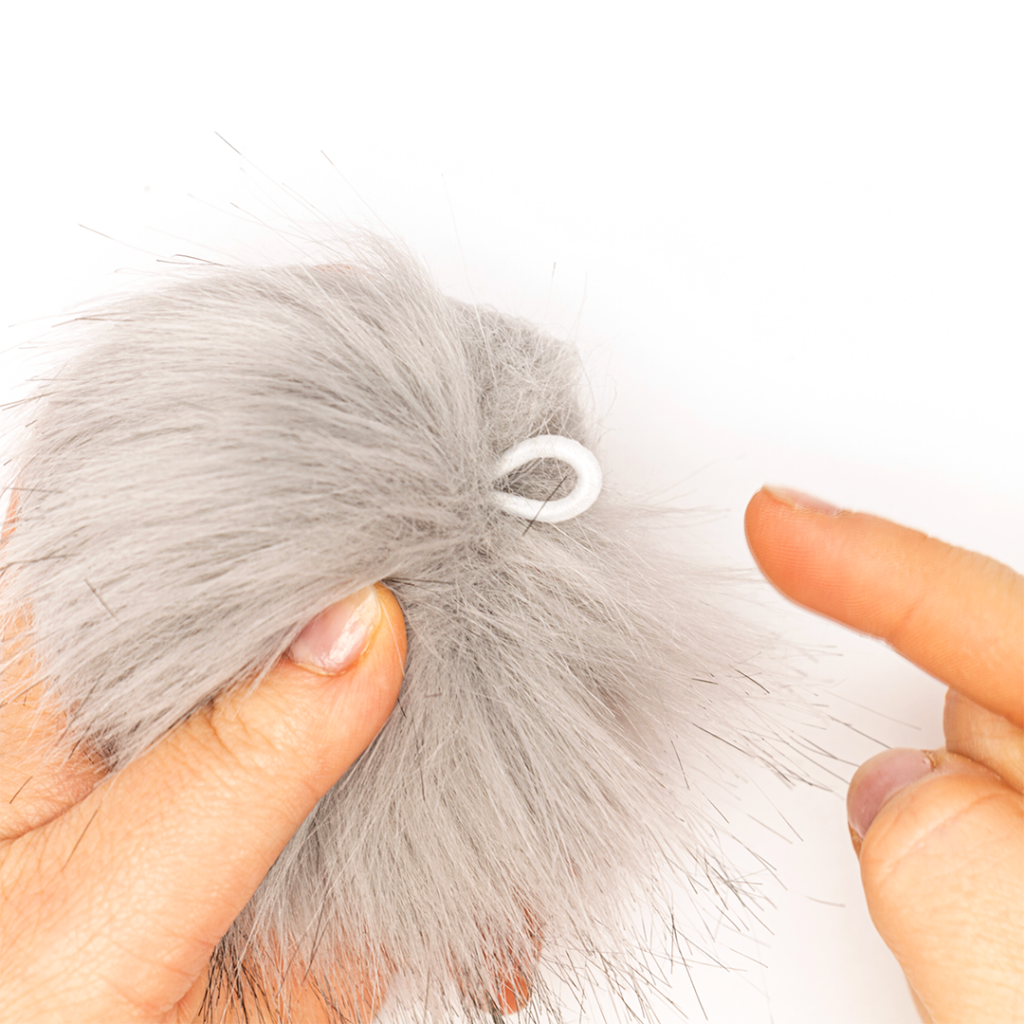 fur pompom showing it has an elastic attachment