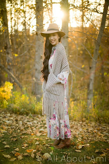 woman modelling a crochet shawl with pockets in the woods.