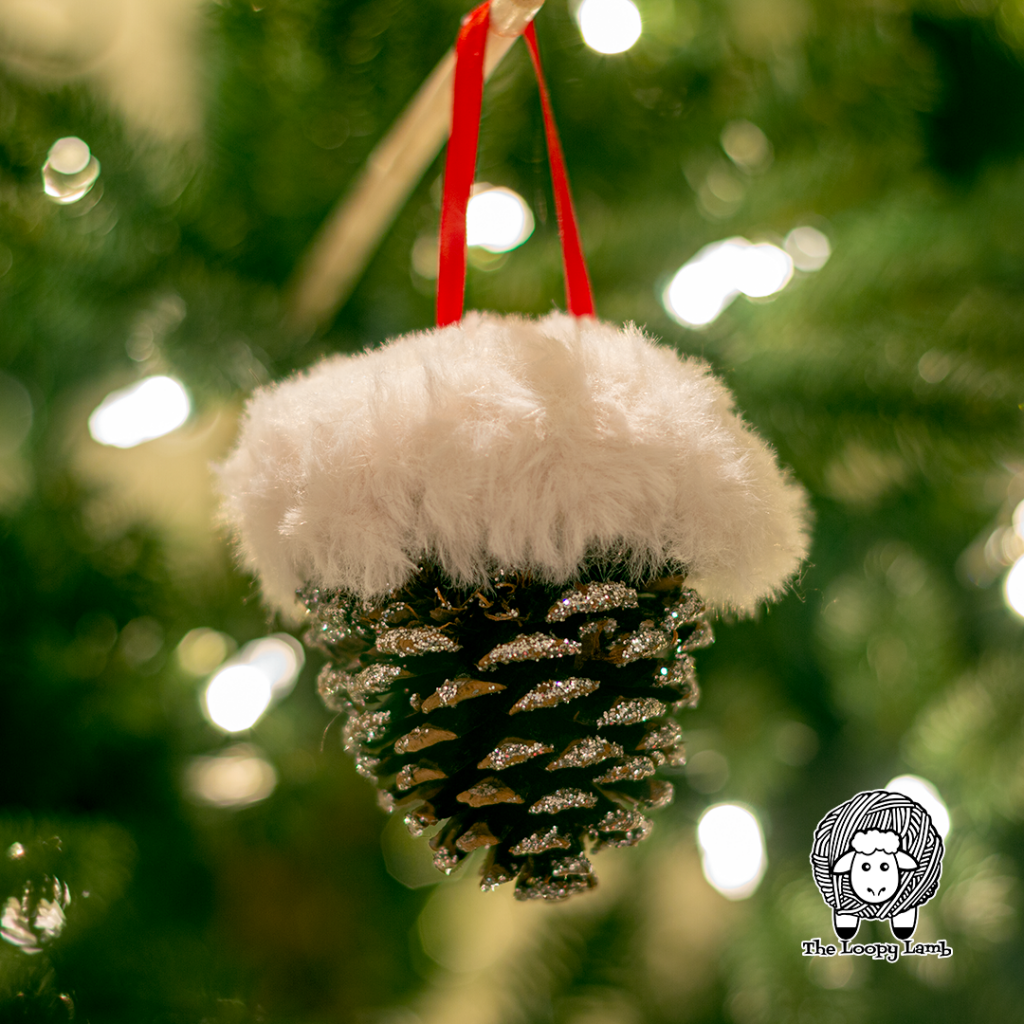 Pinecone ornament made with this Free Crochet Christmas Ornament Pattern hanging in a. tree