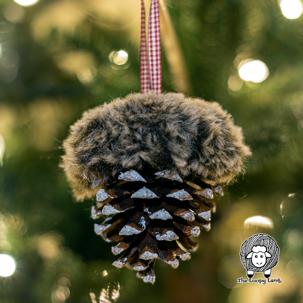 Close up image of a snowy pines ornament with brown fur hanging in a tree