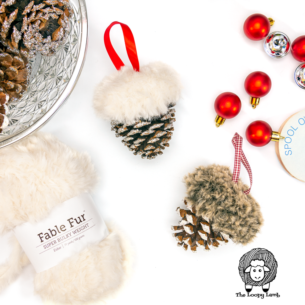 Two Snowy Pines ornaments in a flat lay with Fable Fur and christmas ornaments.