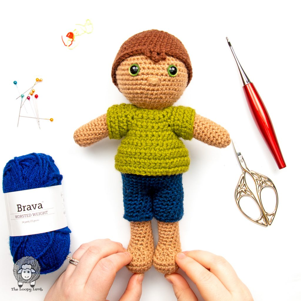 Crochet boy doll wearing crochet doll clothes made with this free crochet pattern