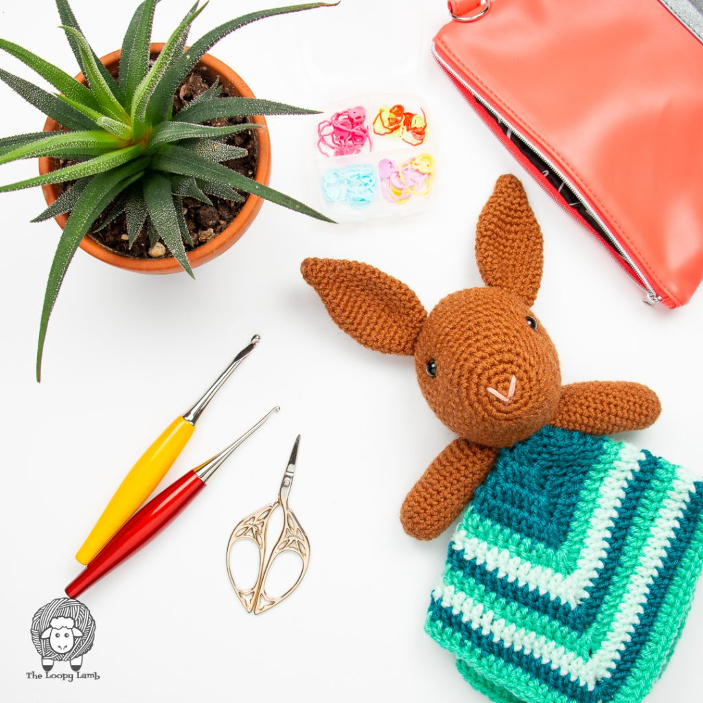 crochet bunny lovey in a flat lay with furls crochet hooks and scissors