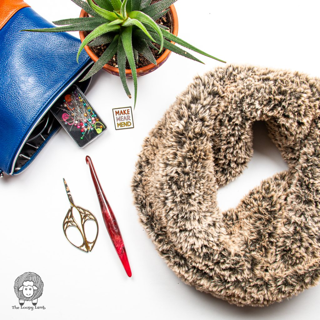 faux fur cowl in a flat lay with a furls crochet hook and scissors
