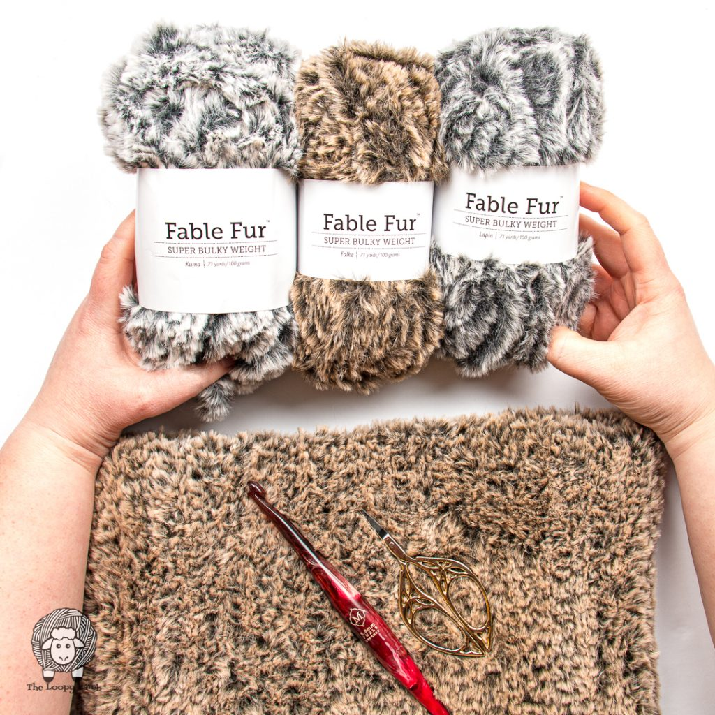 hands holding three different balls of fable fur yarn