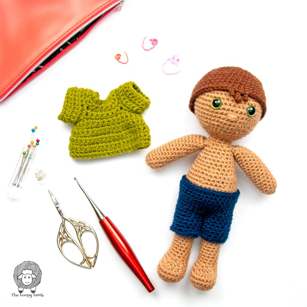 Crochet boy doll wearing shorts made with this Free Amigurumi Doll Clothes Pattern