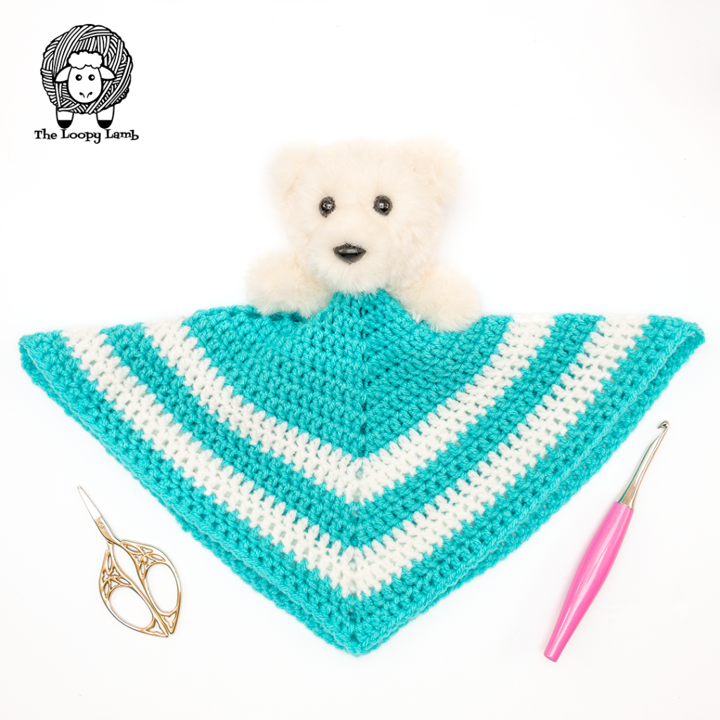 Teddy Bear Lovey in a flay lay with a crochet hook and scissors
