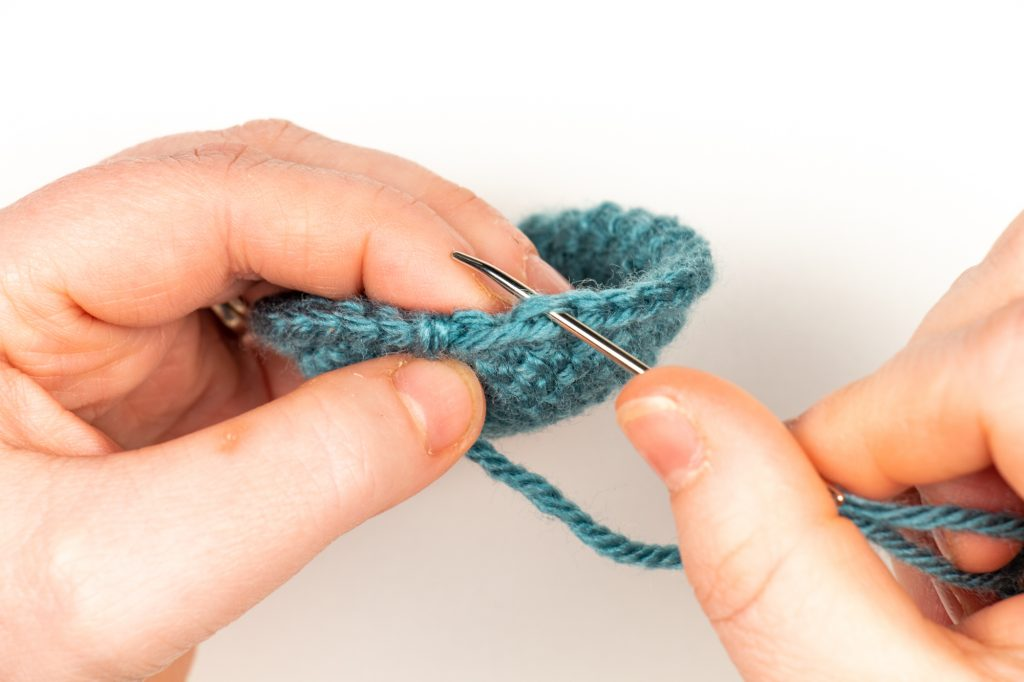 tapestry needle going under the Back Loop of the last stitch
