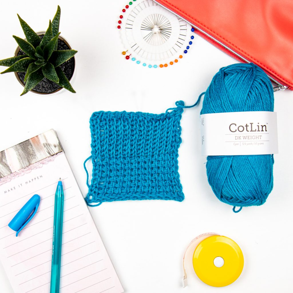 Tunisian crochet sampe swatch in a flat lay with crochet accessories
