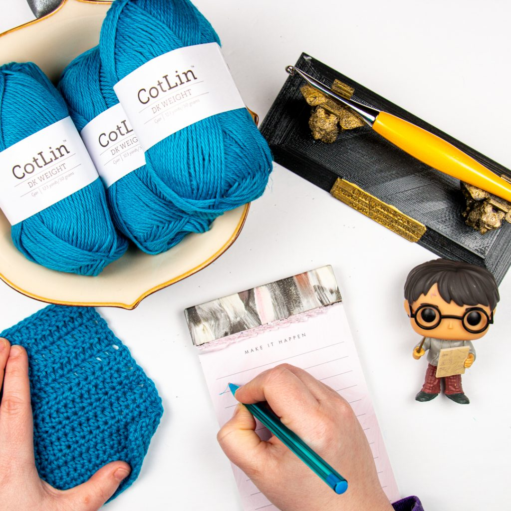 We Crochet CotLin Yarn in a bowl next to a hand making notes about a crochet swatch