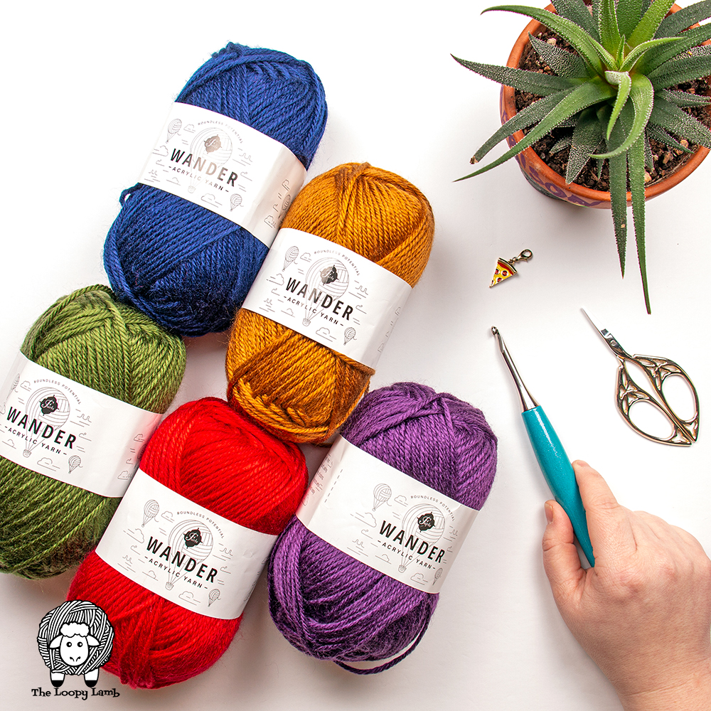 Furls Wander yarn in a flat lay with crochet hook, scissors and pizza stitch marker