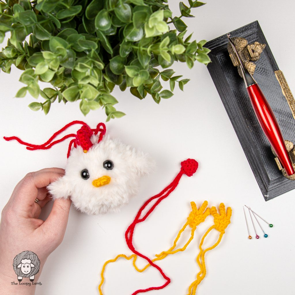 incomplete amigurumi chicken with it's pieces in a flat lay with a furls crochet hook