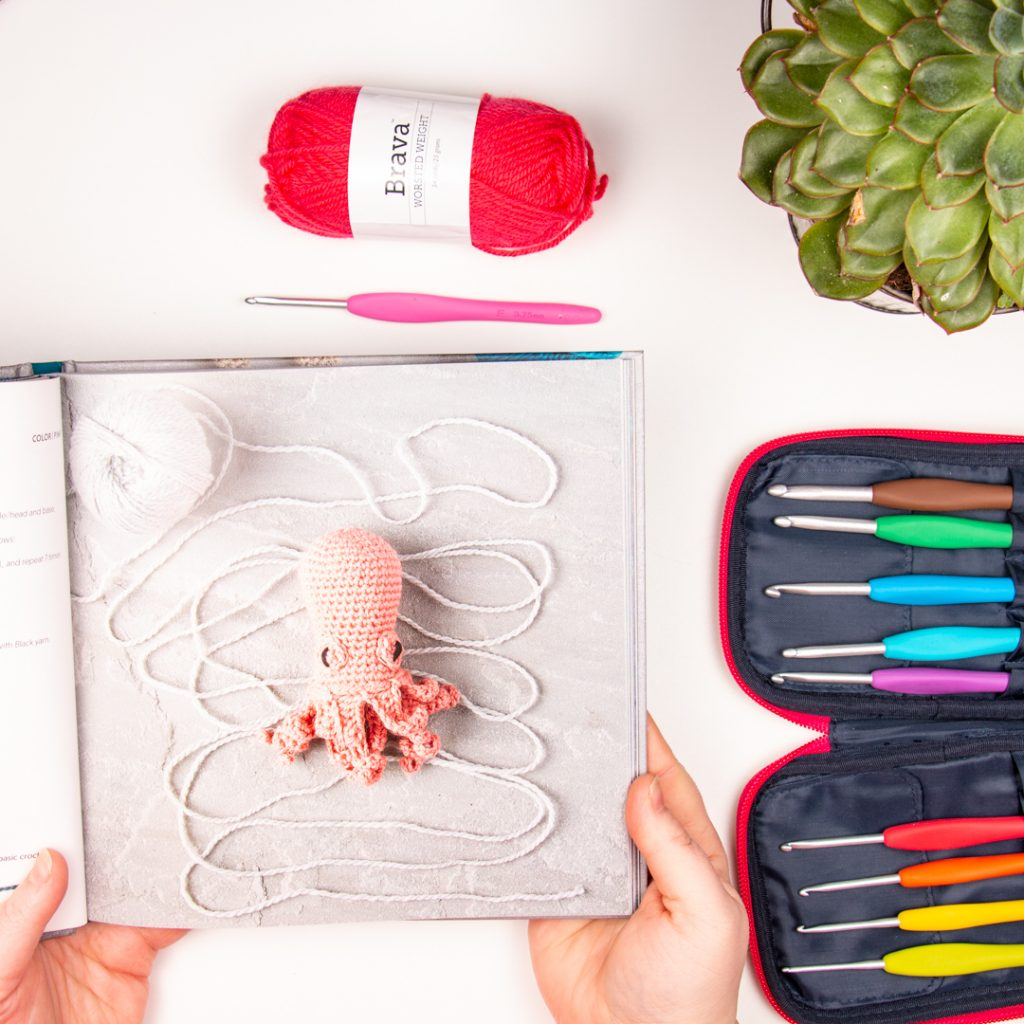 image of a crochet octopus from How to crochet animals: wild in a flat lay with clover amour crochet hooks