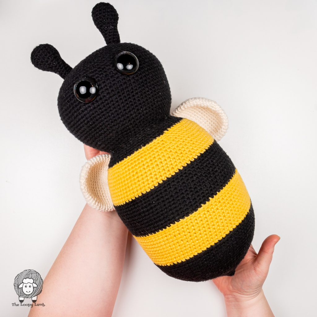hands holding  a giant amigurumi bumblebee made with this free crochet bee pattern