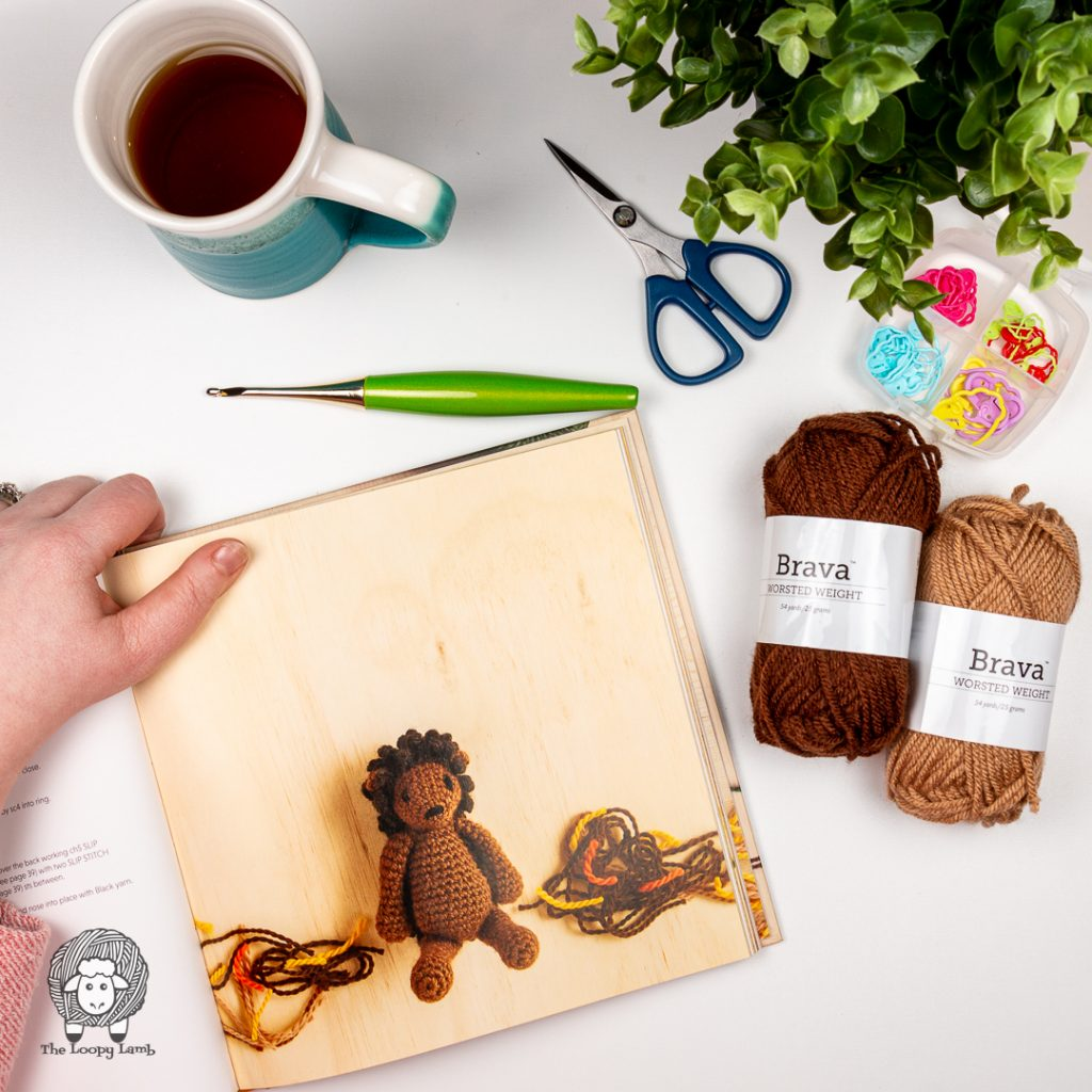 Hedgehog amigurumi toy in the book being reviewed in a flat lay with brava yarn and furls crochet hook